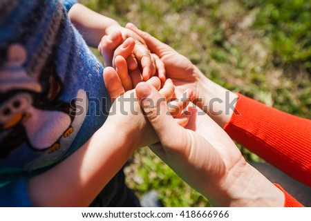 Mom holds child for hands