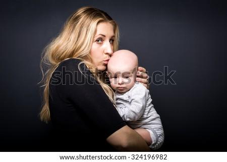 mom hugging newborn baby on black background - stock photo