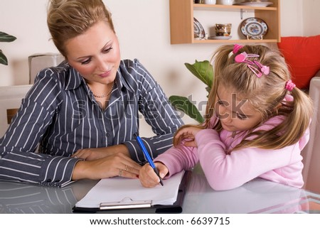 mom is helping her daughter with homework - stock photo