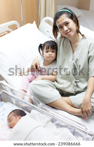 Mom is relaxing with her family after child birth - stock photo