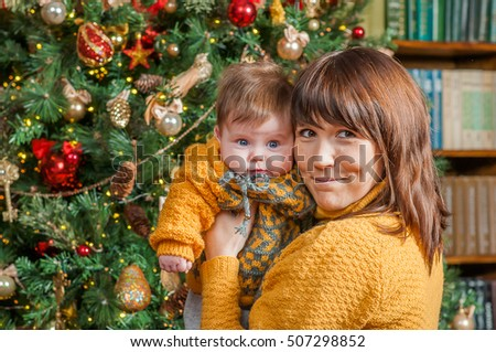 Mom keeps daughter in her arms near the Christmas New Year tree. Daughter is little cute baby