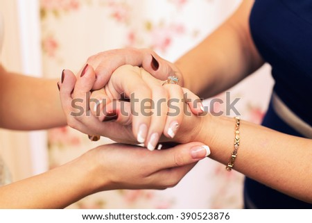Mom keeps her daughter by the hand closeup in the wedding day - stock photo