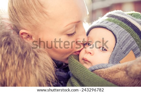 Mom kissing her handsome son - Woman and baby outdoors - stock photo