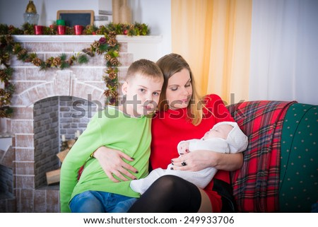 Mom on the couch with the kids. mother, son and baby together on couch at home, apartment interior in winter, winter evening family home