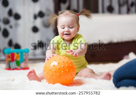 mom playing ball with little daughter at home - stock photo