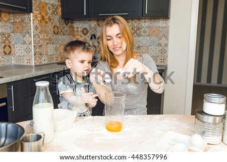 Mom playing with kid in the kitchen. Kitchen is done is dark colors and rustic style. Kid is covered in flour. Mom breaks egg into a jar. Blender, milk, eggs, jars lie on table. - stock photo