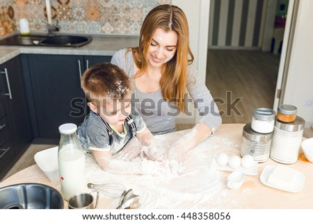 Mom playing with kid in the kitchen. Kitchen is done is dark colors and rustic style. Kid is covered in flour and looks funny. Table is made from light wood. Blender, milk, eggs, jars stand on table. - stock photo