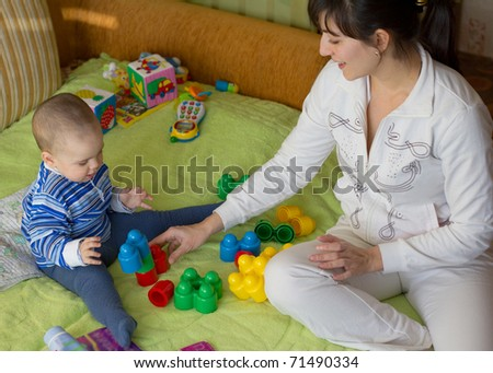 Mom playing with little son - stock photo