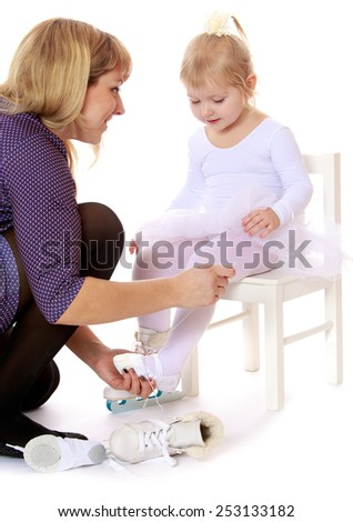 Mom puts on the leg of his little daughter skates.Isolated on white.