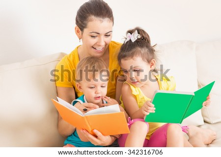 Mom reading a book for children - stock photo