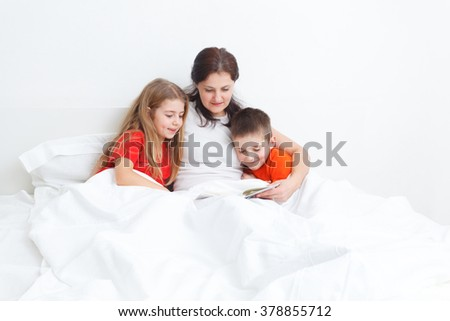 mom reading a book in bed for her kids before sleep - stock photo