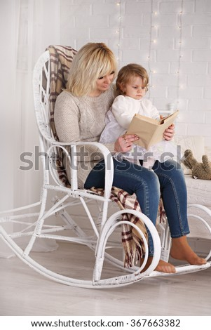 Mom reading a book to a daughter sitting in a wicker chair - stock photo