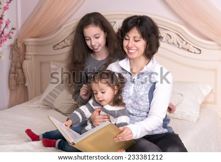 Mom reading a book with children. Little girl holding a big book