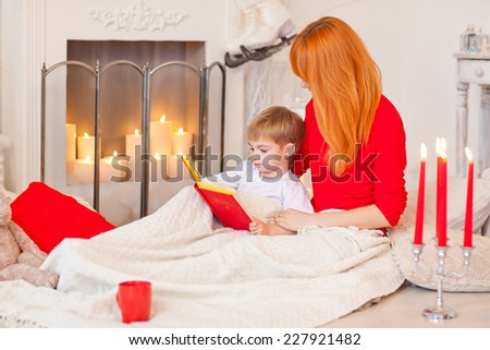 Mom reading bedtime stories for her son. Christmas Eve. Tales of the fireplace.  - stock photo