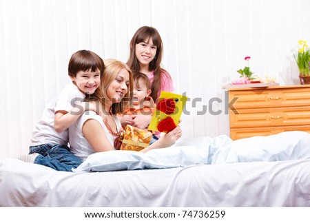 Mom reading greeting card made by kids - stock photo