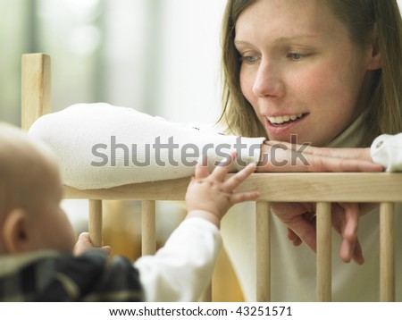 Mom Smiling at Baby Over Playpen Railing. Horizontally framed shot. - stock photo