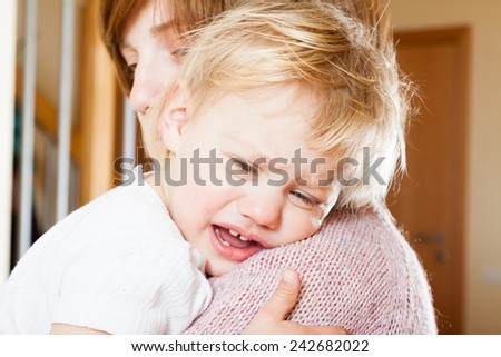 Mom soothing baby daughter in her arms - stock photo