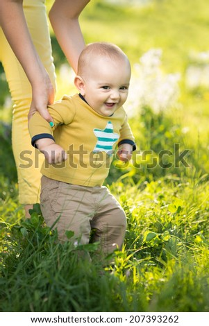 Mom teaches son walking grass on the lawn - stock photo