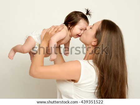 Mom throws baby baby and kiss, play and having fun - stock photo