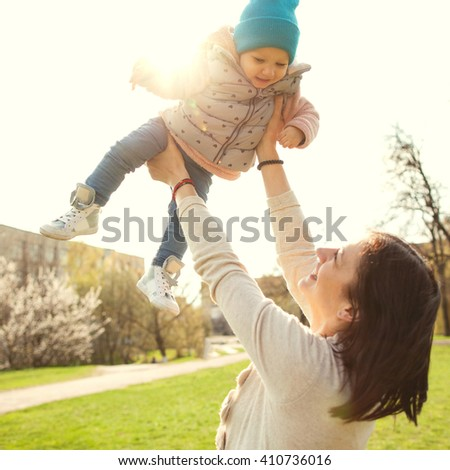 Mom throws baby in up above him, happy together, spring, Mother's Day - stock photo