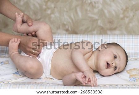 mom vertiginous baby diaper change - stock photo