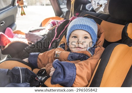 Mom watch at kids Children's safety in a car Son and daughter looking at mother Babes sitting inside modern auto People baby boy look at camera The idea of safe traffic - stock photo