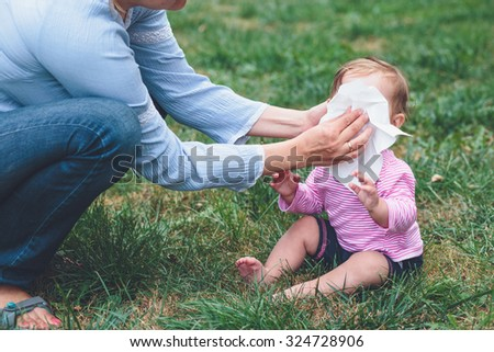 Mom wiping nose her little daughter with a tissue - stock photo