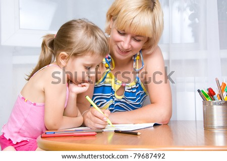 mom with a child draws with pencils - stock photo