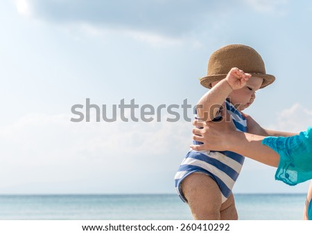 Mom with baby on the beach - stock photo