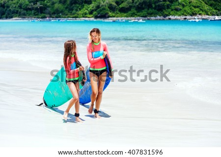 Mom with child are learning surfing together