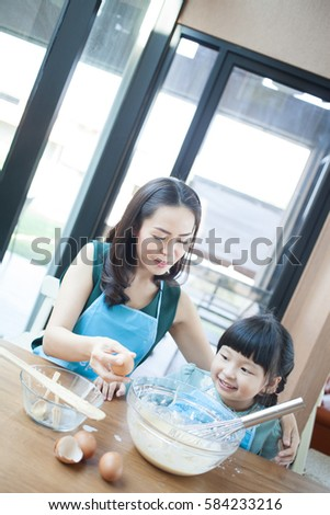 Mom with daughter are cooking in the kitchen to Mothers day, lifestyle photo series in bright home interior . little girl helping her mother prepare food in the kitchen