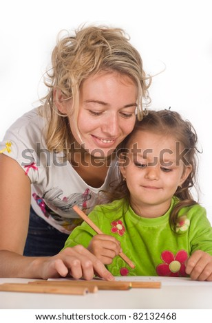 mom with her child drawing at table - stock photo