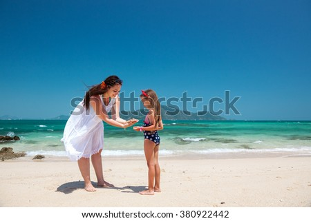 Mom with her kid daughter walking at the tropical beach