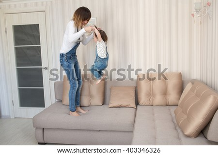 Mom with her  little daughter are relaxing and playing on the sofa - stock photo