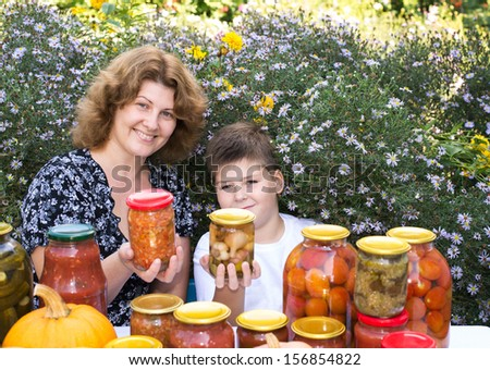 Mom with her son and home canned vegetables - stock photo