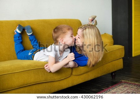 Mom with her 5 years old child spend time together, casual lifestyle photo series in real life interior Mom and son lying and laughing on yellow sofa - stock photo