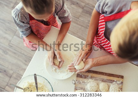 Mom with her 9 years old daughter are cooking in the kitchen to Mothers day, lifestyle photo series in bright home interior, top view point - stock photo