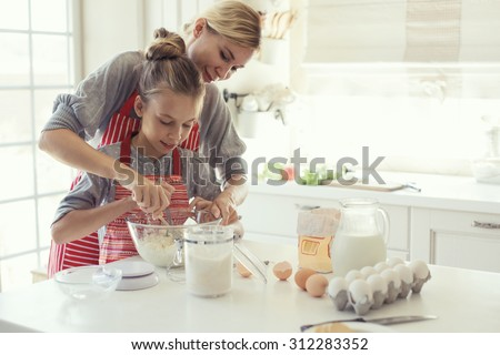 Mom with her 9 years old daughter are cooking in the kitchen to Mothers day, lifestyle photo series in bright home interior - stock photo