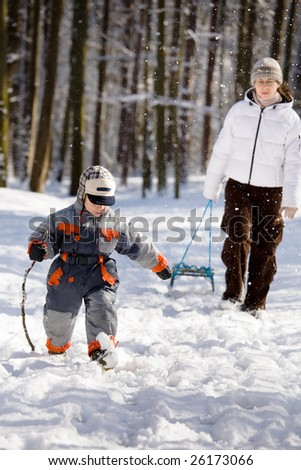 Mom with his son on a walk in the woods in winter