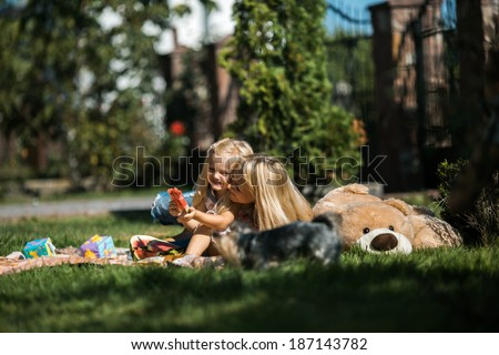 Mom with kids on the grass - stock photo