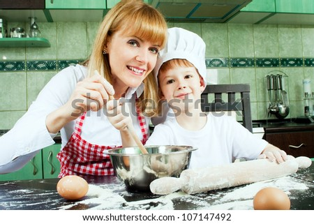 Mom with son cooking and baking in kitchen - stock photo