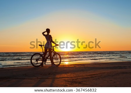 Moment in time. Young sporty woman cyclist silhouette contemplating the sunset on blue sky background on the beach. Summertime multicolored outdoors horizontal image with filter. - stock photo
