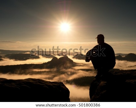 Moment of loneliness. Man with cap sit on the peak of rock and watching into colorful mist and fog in forest valley. Dreamy autumn landscape