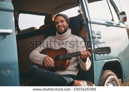 Moment of real joy.  Handsome young man playing guitar and smiling while sitting in blue retro style mini van