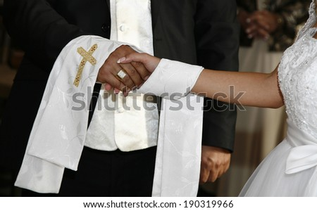 Moment of wedding ceremony with the blessing cloth, focus on hands - stock photo