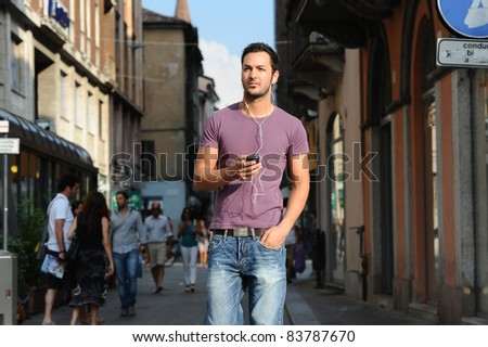 moments of reflection of a guy who walks around the city listening to the music of his mp3 - stock photo