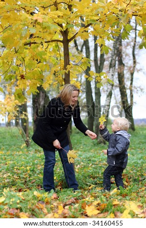 Mommy and little son the autumn park - stock photo