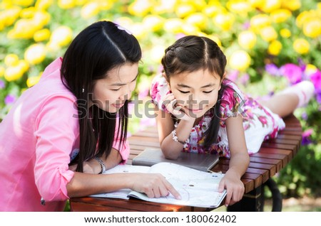 Mon and baby take a home work on the green nature and flower garden. - stock photo