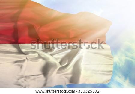 Monaco waving flag against blue sky with sunrays - stock photo