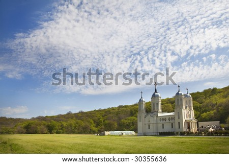 monastery in plain in front of a forest